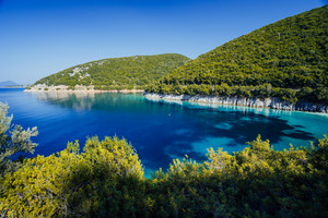 Stunning seaside scenery of the cove with turquoise calm sea water, surrounded by hills overgrown with pine and olive trees. White limestone cliffs reflecting in the crystal clear water