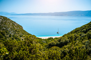 Stunning view of Fteri beach with white sailboat in hidden bay, Kefalonia, Greece. Surrounded by mediterranean vegetation. trekking path. Amazing seascape