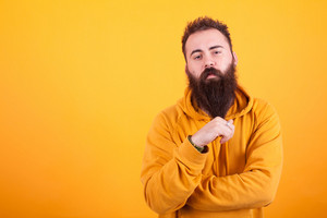 Stylish beaded hipster looking serios at the camera and playing with his beard over yellow background, Yellow hoodie. Cool man. Trendy adult.