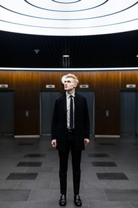 Stylish blond-haired businessman looking upwards while standing in office lobby with creative interior design, full length portrait