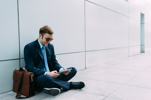 Stylish businessman using digital tablet while sitting on the floor