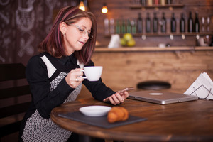 Successful adult businesswoman looking at her phone while having a cup of coffee in a vintage pub