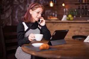 Successful adult businesswoman talking on her phone while holding a cup of coffee. Vintage restaurant