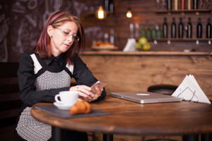 Successful businesswoman checking her phone next to french croissant. Cozy vintage restaurant