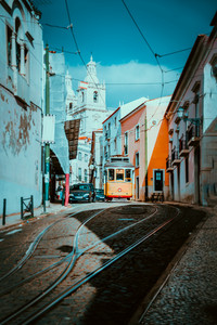 Summer cityscape of Lisboa. Red tram going down the hill along old traditional houses. sunny afternoon, narrow streets, cobblestones winding road, vacation in Lisbon