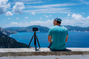 Summer holiday visiting Greece. Male freelance photographer enjoying capturing time lapse moving cloudscape coastline and Mediterranean sea with camera on tripod. Europe travel