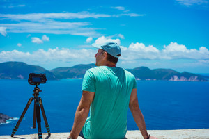 Summer holiday visiting Greece. Male photographer enjoying to capture time lapse cloudscape, coastline and sea with digital camera on tripod. Europe travel