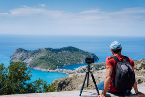 Summer holiday weekend visiting Greece Europe. Male freelance photographer with backpack enjoying capture time lapse of Mediterranean village Assos from top view point platform. Camera on tripod