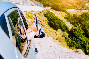 Summer road trip car vacation concept. Woman legs out the window in car on the winding road of greek island