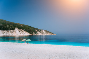 Sun beach umbrellas on a pebble beach with azure blue calm sea, white rocks and clear sky in background