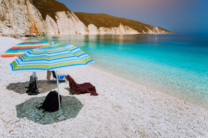 Sun beach umbrellas on a pebble beach with calm azure sea water, white cliff rocksy coastline and clear blue sky in background