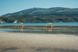 Sunlougers below umbrellas in the shallow water of turquoise bay. Opposite mountainous island with windmills on the top