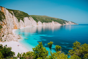 Sunny Fteri beach lagoon with rocky coastline, Kefalonia, Greece. Tourists under umbrella chill relax near clear blue emerald turquoise sea water