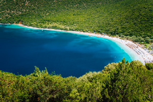 Sunny summer day on Antisamos beach on Kefalonia island, Greece. Crystal clear water, huge hills beautiful white beach, picturesque nature. Stunning view of mediterranean coastline