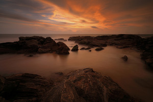 Sunset on the coast. Sea with sun. Rock coast with sun during sunset. Sunset at Bentota, Sri Lanka, Asia. Beautiful landscape with orange sun and sea. Evening on sea with orange sunset in Ocean.