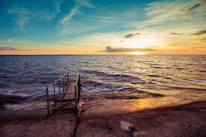 Sunset over the seashore with concrete embankment and small pier