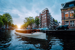 Sunset scene in Amsterdam city. Great Tourist boat on the famous Dutch canal floating tilted houses. Colorful evening landscape in Netherlands, Europe