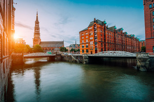 Sunset view on the old town with canals and metal arch bridges, Saint Catherine's church and Warehouse district in Hamburg city, Germany