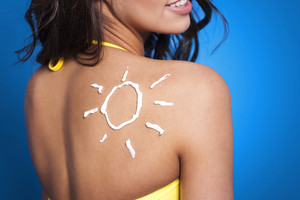 Suntan lotion on woman's arm in sun shape