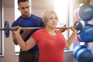 Supporting instructor exercising with mature woman