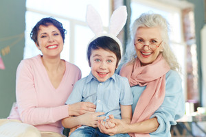 Surprised boy and his mother and grandmother looking at camera with smiles