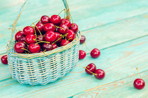 Sweet cherries in a basket on a wooden table