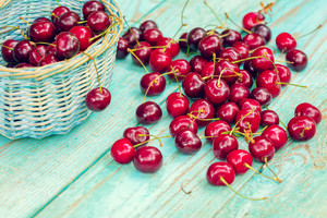 Sweet cherries scattered out of a basket on a wooden table