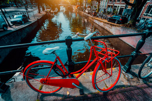 Symbols of Amsterdam: Red Bicycle parked on a bridge, Netherlands. Travel, romance, vacation, culture concept