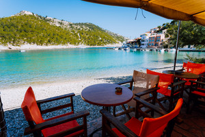 Tables with chairs of cozy Greek tavern restaurant in front of the beach in Assos village on Kefalonia island in Greece on summer morning