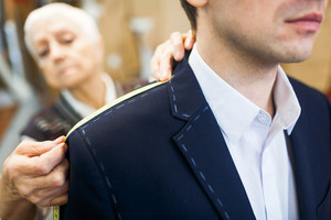 Tailor measuring shoulder length of male jacket