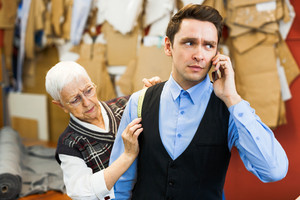 Tailor measuring shoulder of businessman speaking on cellphone