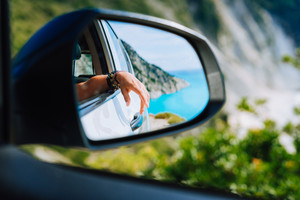 Tanned female hand in the car side view mirror. Blue mediterranean sea and white rocks landscape in background