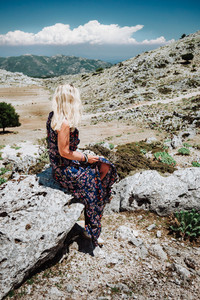 Tanned girl in beautiful dress sitting alone on the stone in the mountainous scenery of highland countryside of greek island. Rocky stones and mountains landscape. European holidays concept