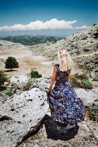 Tanned girl in front of panorama of highland countryside and beautiful nature. Rocky stones and mountains landscape