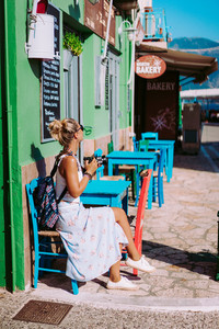 Tanned young woman with camera on vacation in Greece exploring cozy narrow alleys in greek town. Lovely exited girl sitting in street cafe and enjoying summer day. European holidays concept