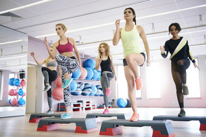 Team of women having step aerobics class