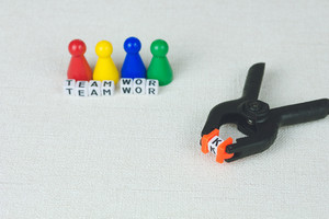Team work concept - Figures in the line and an clamp tool as symbol for a working labor team collaboration
