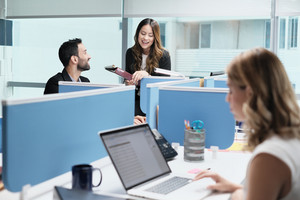 Teamwork with colleagues working and talking in modern office. Busy girl, man and woman at work in coworking space and meeting as co-workers. Business people, worker, job and profession