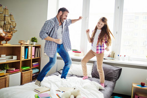 Teenage daughter and her bearded father having fun in bedroom: they dancing and jumping on bed with grey and white bedclothes