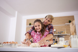Teenage girl and her mother smiling while they are cooking together. Parent love.
