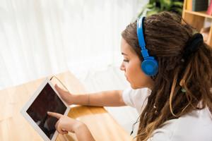 Teenage girl in headphones using a digital tablet