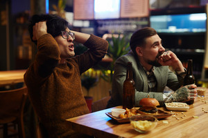 Tense football fans watching match broadcast in pub