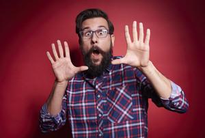 Terrified man gesturing at studio shot