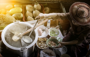 thai noodle food making on floating boat in floating market thailand