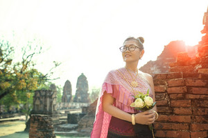 thai woman toothy smiling face standing with pink lotus flower bouquet in hand