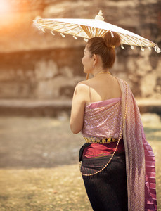 thai woman wearing old tradition clothes style with bamboo umbrella standing in ancient location
