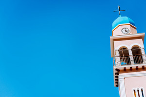 The blue dome of a greek church with bell tower against a deep blue sky