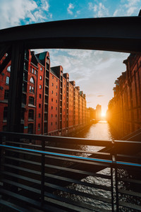 The red brick warehouse - Speicherstadt district in Hamburg Germany, framed by steel bridge arch beams with canal perspective filled by warm sunset light