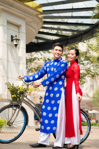 The Vietnamese in traditional clothes posing with bicycle