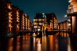 The Warehouse District - Speicherstadt at night. Tourism landmark of Hamburg. View of Wandrahmsfleet in light of lantern lamp. Port of Hamburg within the HafenCity quarter